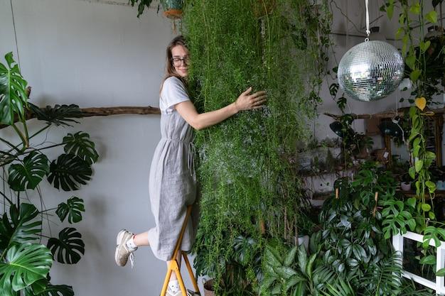 꽃가게에서 무성한 아스파라거스 양치식물을 껴안고 선취특권 드레스를 입은 행복한 젊은 여성 꽃집. 웃는 정원사 여성 포옹 houseplant. 집에서 녹지. 식물의 사랑. 아늑한 실내 정원.