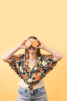 Happy young woman in flowered shirt holding orange halves covering her eyes on yellow background.