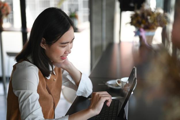 Счастливая молодая женщина-фрилансер, сидя в деревянном баре в кафе