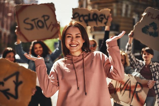 길에서 여성 활동가 그룹과 함께 생태에 대해 항의하면서 몸짓을 하는 행복한 젊은 여성