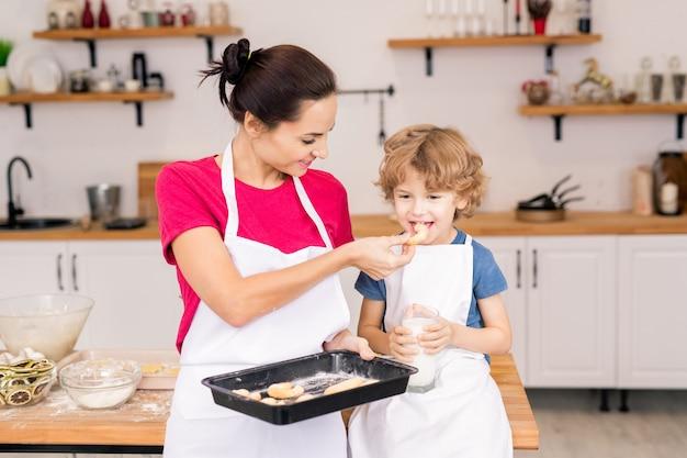 台所に座っている間、彼女の幼い息子にトレイから焼きたてのクッキーを与える幸せな若い女性