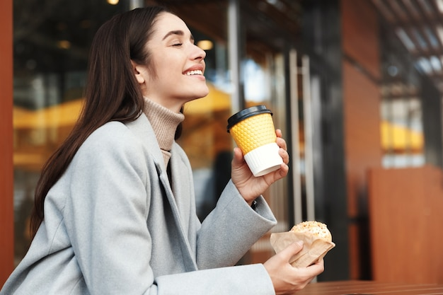 Happy young woman in grey coat eating a donut in a coffee shop.