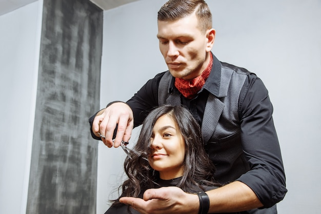 Happy young woman and hairdresser cutting hair tips at salon.