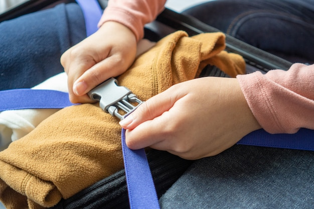 Happy young woman hands packing clothes into travel luggage on bed