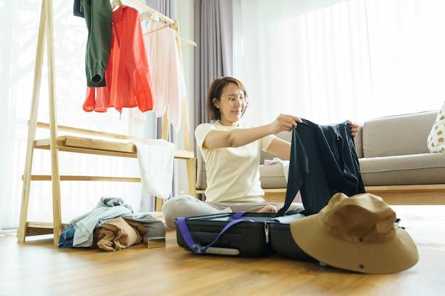 Счастливая молодая женщина вручает упаковку одежды в дорожный багаж на кровати дома