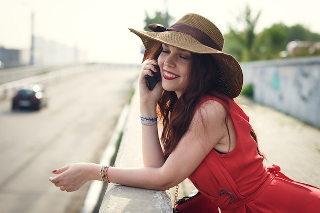 A happy young woman in a hat is walking in the summer with a bag and talking on the phone