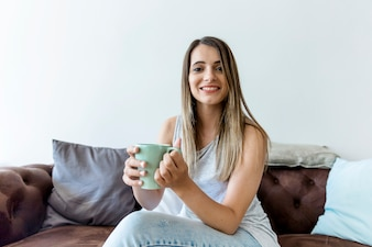 Happy young woman having a coffee