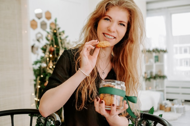 Happy young woman having eating christmas cookies in kitchen and smiling