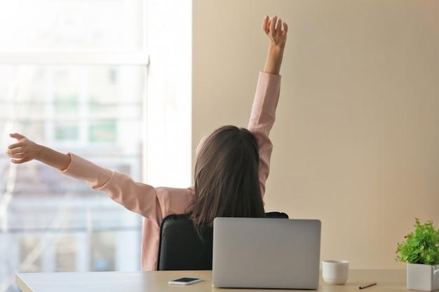 明るい部屋の職場で短い休息を持っている幸せな若い女性