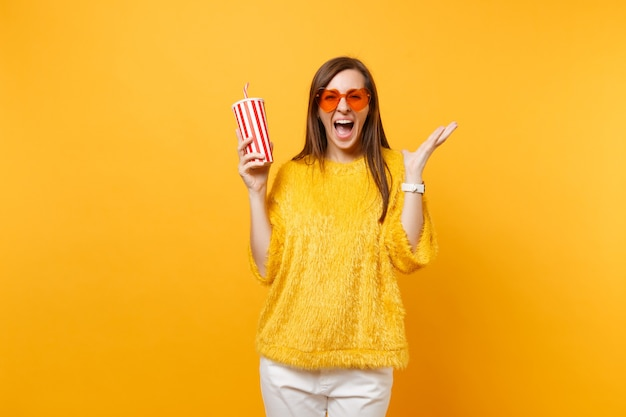 Happy young woman in heart orange glasses spreading hands, screaming, holding plastic cup with cola or soda isolated on yellow background. people sincere emotions, lifestyle concept. advertising area.