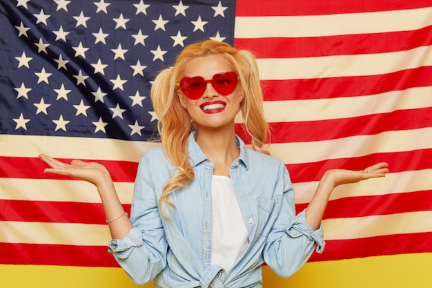 Happy young woman in heart shape sunglasses on usa flag  background.