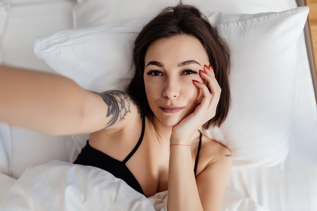 Happy young woman hold smart phone lying awake in bed in morning doing selfie top view