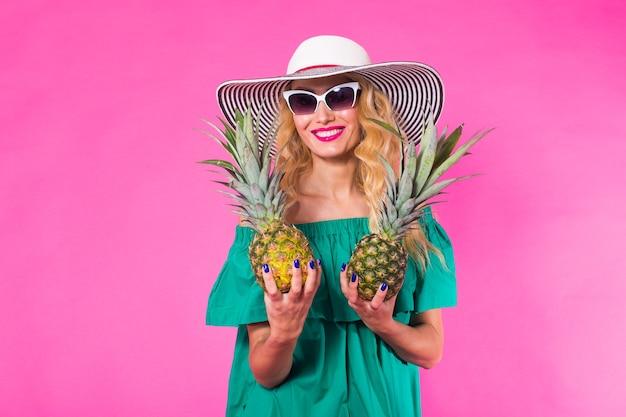 Счастливая молодая женщина, держащая ананас на розовом фоне. концепция лета, диеты и праздников