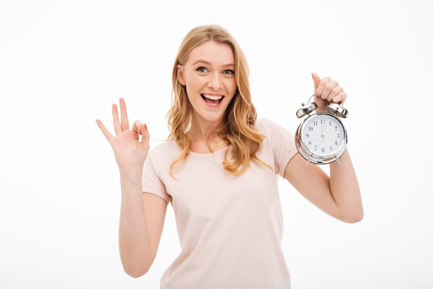 Happy young woman holding alarm clock showing ok gesture.
