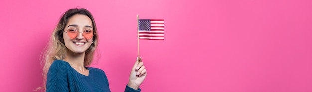 Счастливая молодая женщина, держащая американский флаг на студийном розовом фоне