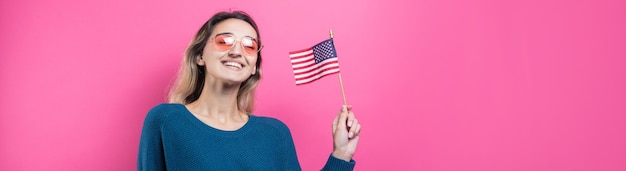 Happy young woman holding american flag against a studio pink background