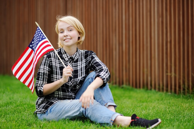 Happy young woman holding american flag. independence day concept.