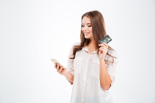 銀行カードと白い壁で隔離のタブレットコンピューターを保持している幸せな若い女性