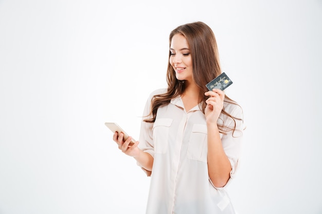 Happy young woman holding bank card and tablet computer isolated on a white wall
