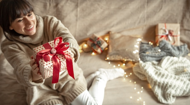 Happy young woman holding a beautifully wrapped christmas present. new year and christmas celebration concept.