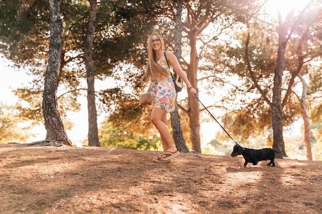 庭で彼女の犬と一緒に歩く本を持っている幸せな若い女性