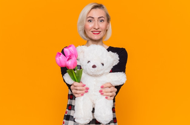 贈り物としてチューリップとテディベアの花束を保持している幸せな若い女性