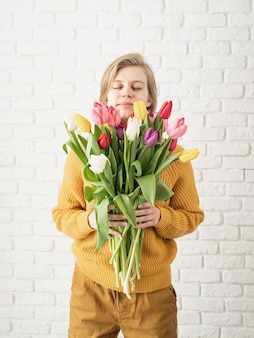 Happy young woman holding bouquet of tulips