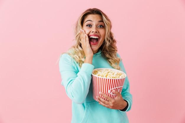 Счастливая молодая женщина держит ведро с попкорном и смотрит в камеру, изолированную над розовой стеной