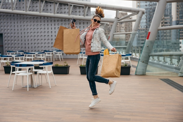 Happy young woman holding coffee cup, jumping with grocery shopping paper bag with long white bread baguette