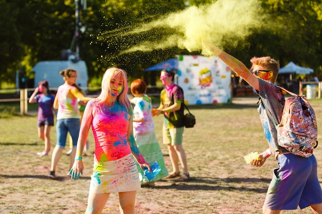 Happy young woman holding colorful paint in hands and smiling at holi festival