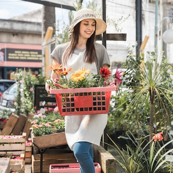 Happy young woman holding container with beautiful flowers