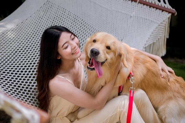 개 골든 리트리버를 들고 행복 한 젊은 여자.