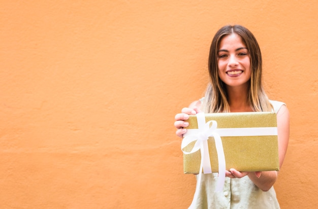 Happy young woman holding gift against orange wall