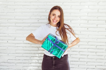 Happy young woman holding gift box in front of brick wall