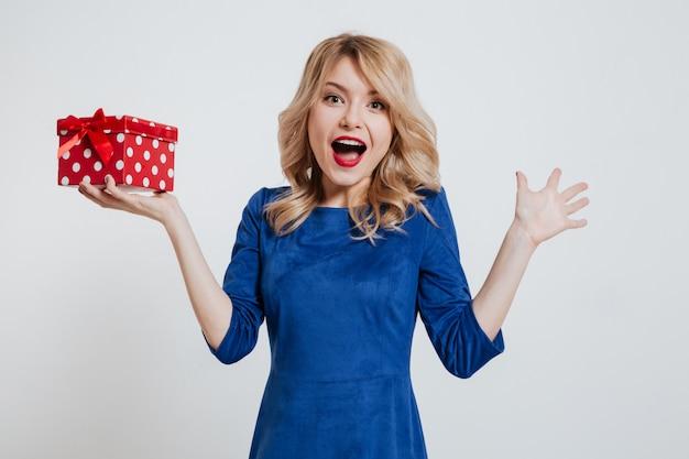 흰 벽에 선물 상자를 들고 행복 한 젊은 여자