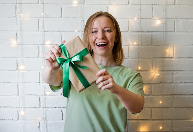 Happy young woman holding a gift box over white brick background