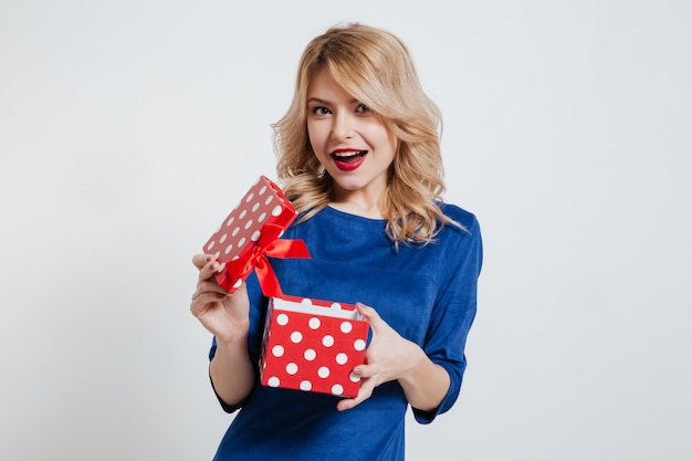Happy young woman holding gift box over white wall