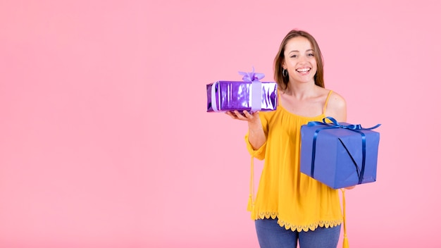 Happy young woman holding gift boxes against pink background