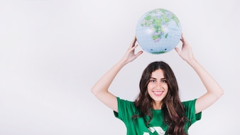 Happy young woman holding globe over her head