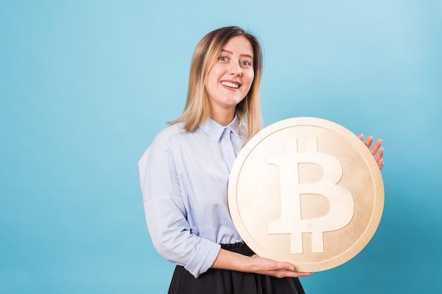 Счастливая молодая женщина, держащая золотой биткойн, подмигивая, думая о криптовалюте.
