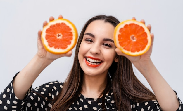Happy young woman holding grapefruit halves near face. cheerful smile with red lips.
