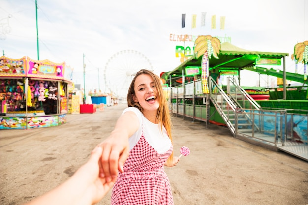 Happy young woman holding hand of her boyfriend at amusement park