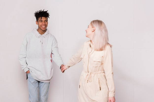 Happy young woman holding hand of her boyfriend looking at her boyfriend against white background
