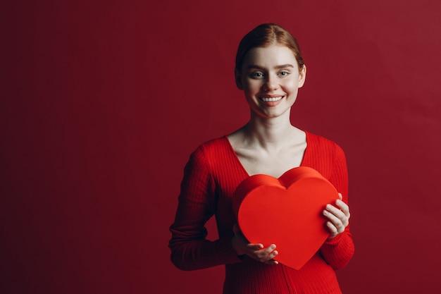 赤い背景でバレンタインデーにハート型のボックスを保持している幸せな若い女性