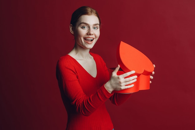 Happy young woman holding heart shaped box and surprised in valentines day at red background
