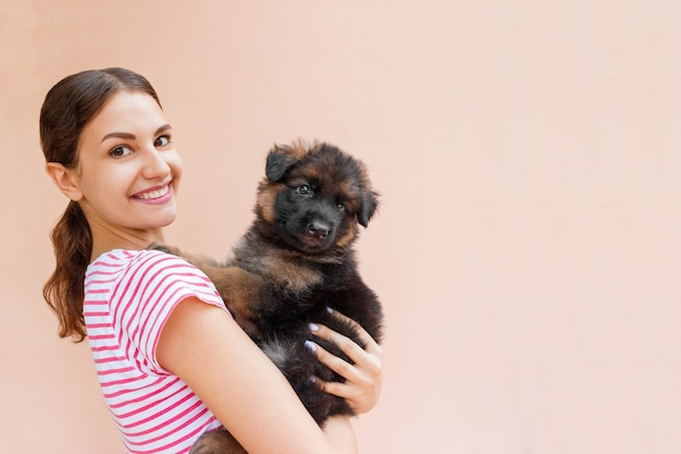 Happy young woman holding her pet puppy on orange background.