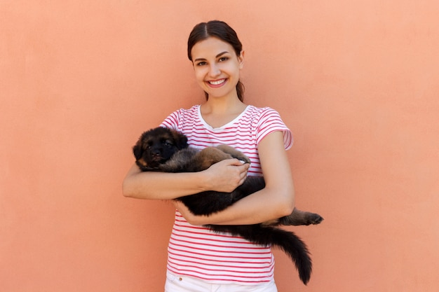 Happy young woman holding her pet puppy on orange background