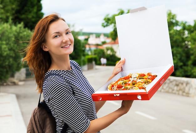 유럽 거리에서 야외 상자에 뜨거운 피자를 들고 행복 한 젊은 여자