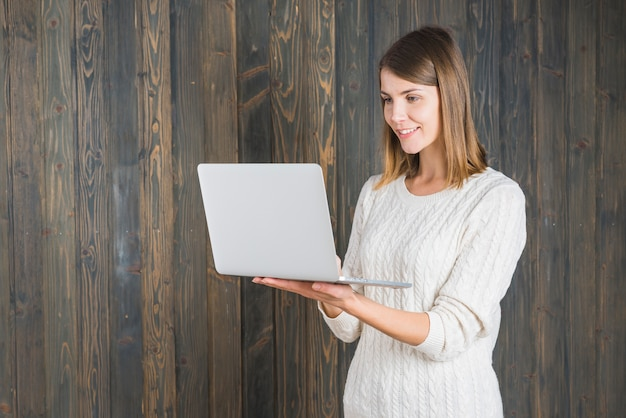 Happy young woman holding laptop against wooden background