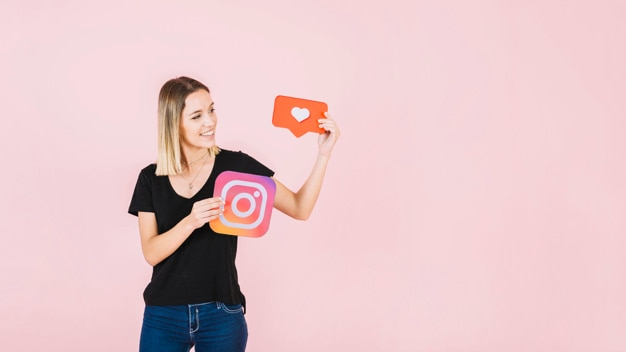 Happy young woman holding like and instagram icon